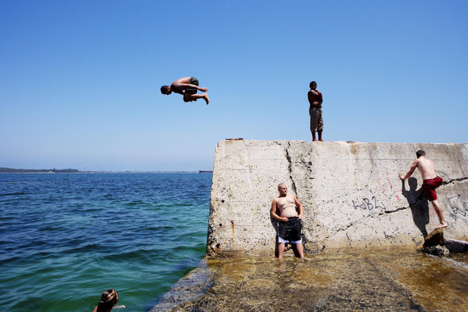 Young people jumping off wall at The Suction, Botany Bay.