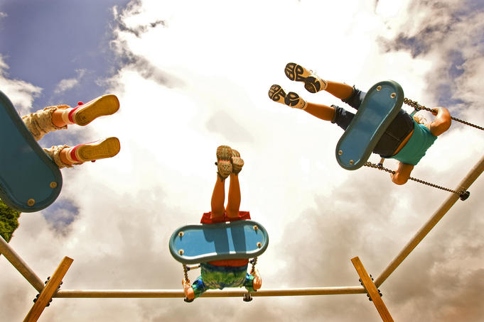 Children playing on swings from below.
