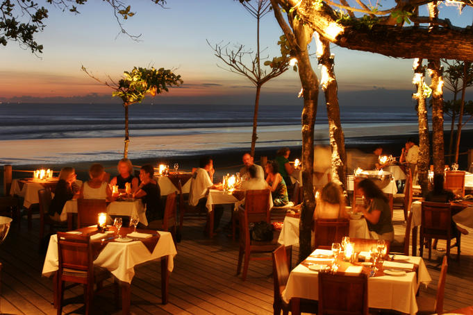Diners at sunset in beach restaurant.