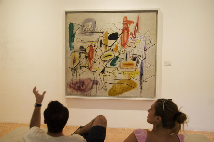 Visitors watching a Gorky's painting in the Peggy Guggenheim Collection.
