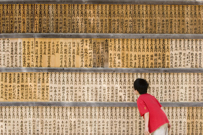 Young boy reading inscriptions on wall of wooden tablets.