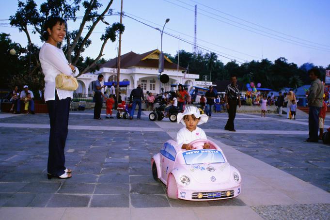 Mother smiling at girl in toy beetle car at dusk, with families behind.