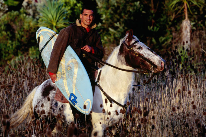 Local Maori surfer carrying his surfboard while on horseback.