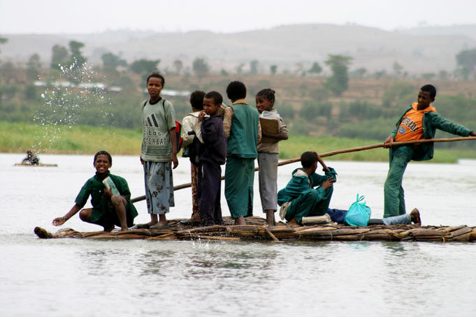 Boy poles his schoolfriends across Blue Nile on papyrus canoe.