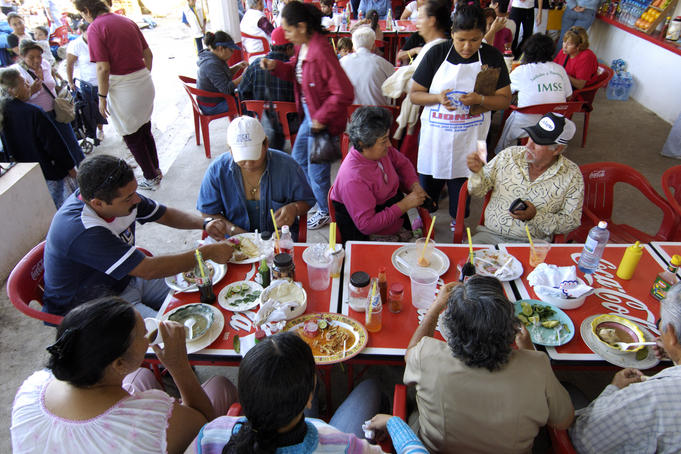 Outdoor restaurant patrons enjoying Sunday afternoon lunch (almuerzo) during religious festival in Tepic.
