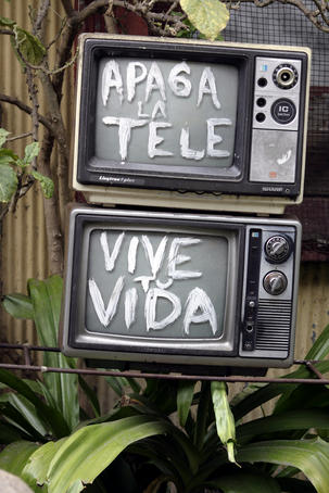 Television sculpture in someone's front garden, 'turn off the TV and live your life'.