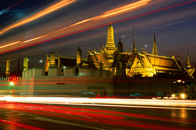 Car lights and Wat Phra Kaew (Temple of the Emerald Buddha) at night.
