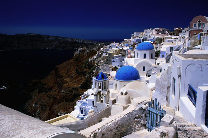 White-washed houses and blue domes on cliff top.