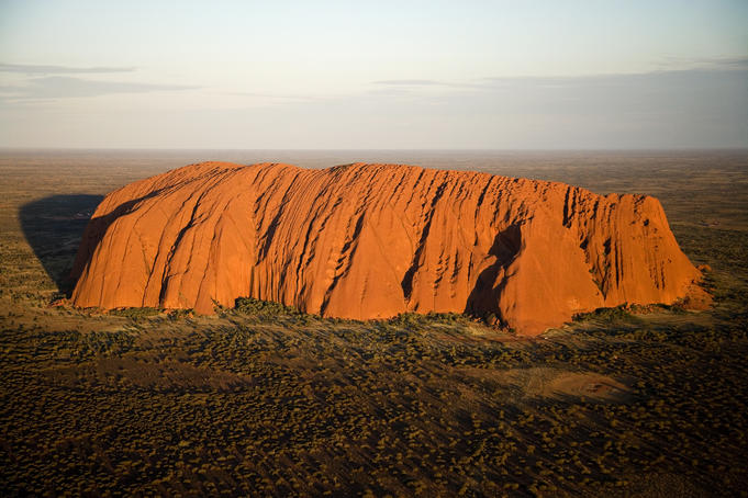 Aerial of Uluru (Ayers Rock) in late afternoon light.