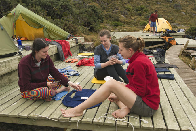 Bushwalkers relaxing, playing cards, on remote area camping platform, Western Arthur Range.