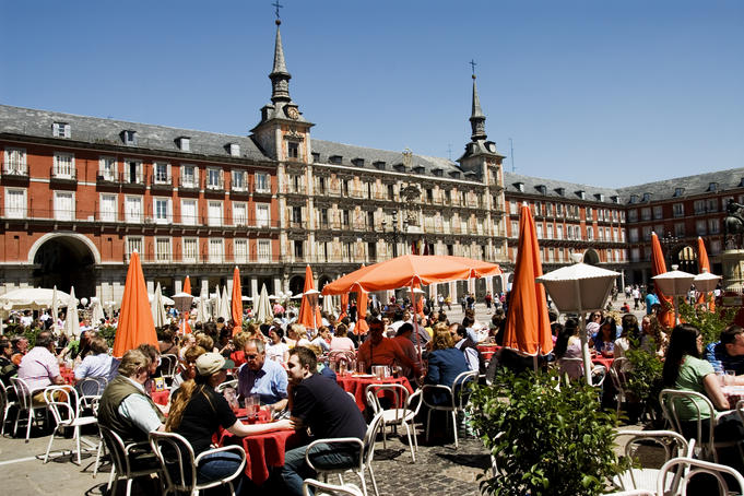 Open-air cafes on Plaza Mayor with Real Casa de la Panaderia in background.