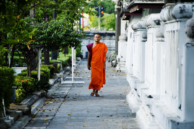 Monk walking on footpath.