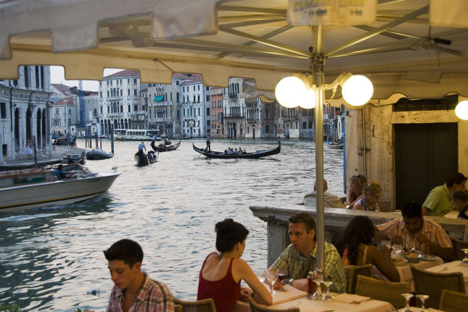 Alfresco diners on bank of Grand Canal near Rialto Bridge.