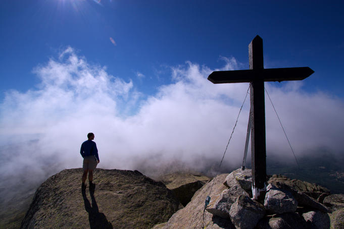 Man looking into mist-covered valley, with burnt crucifix in foreground.