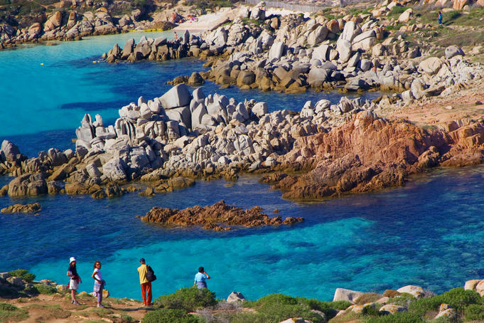 Tourists admiring blue waters of Corsica's coastline.