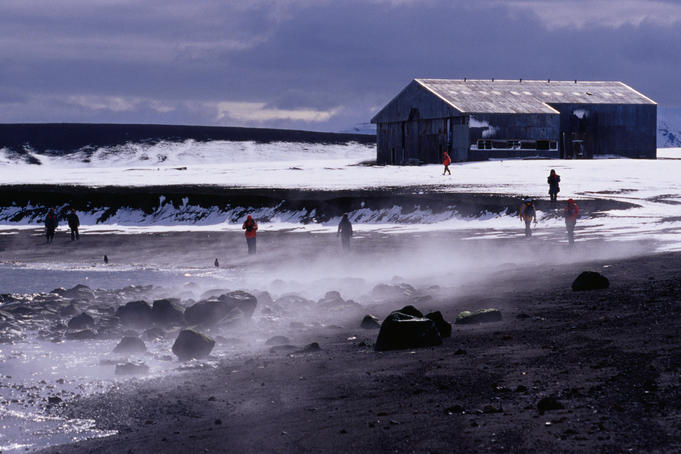 Tourists on beach in front of derelict aircraft hangar, Whalers Bay.