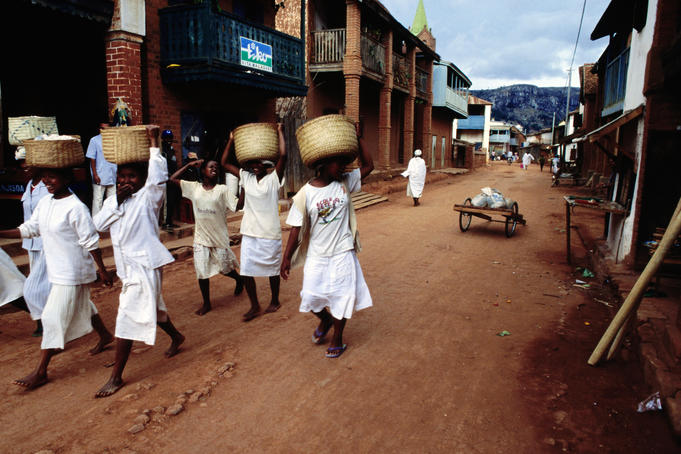 Women of a religious community carry baskets on their heads through the Soatanana village.