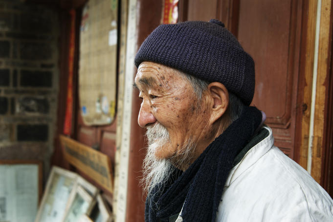 Portrait of Dr Ho, a noted herbalist well known to foreign visitors outside his clinic in Baisha Village.