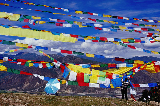 Pilgrim stringing up prayer flags with mountains in background.