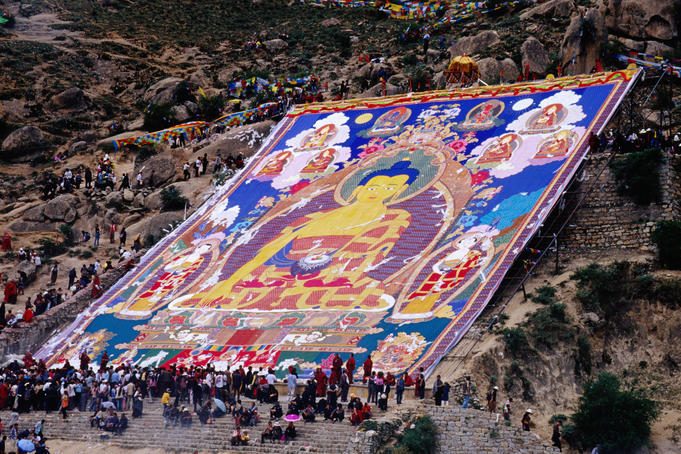 Pilgrims attending annual celebration of hanging of huge thangka, Drepung Monastery.