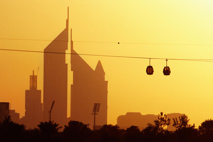 Creekside Park cable cars (gondolas) passing the Emirates Towers at sunset.