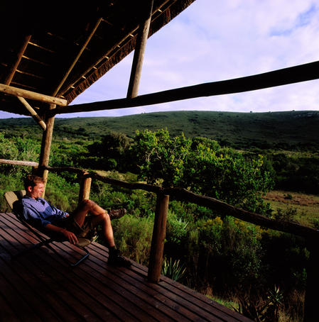 Man relaxing on hotel balcony and looking over grasslands.