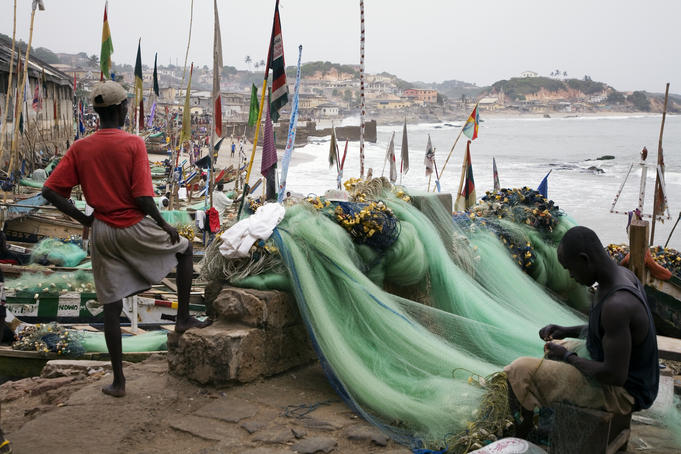 Fisherman mending nets with boats and town in background.