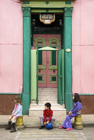 Children sit in front of a colourful house in hillside of city.