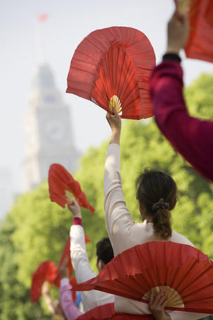 Women practising tai chi with fans on the Bund.