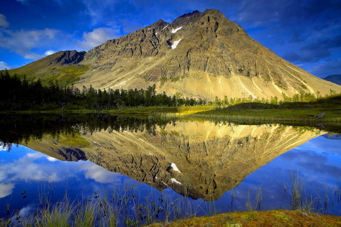 Mount Storetinden mirrors itself in a small lake, Lyngsalpene.