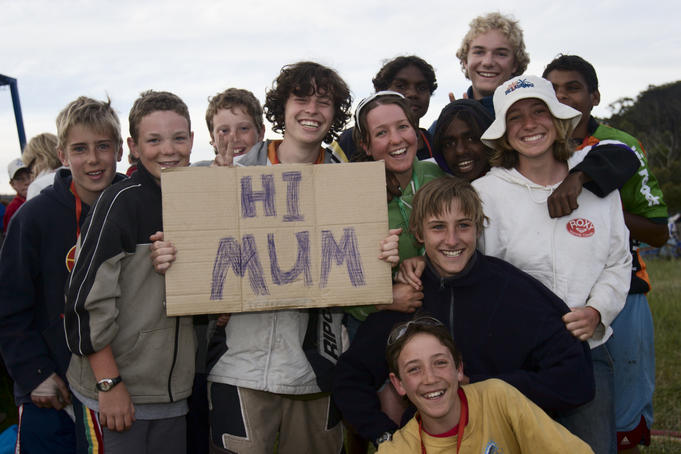Children holding up 'Hi Mum' sign.
