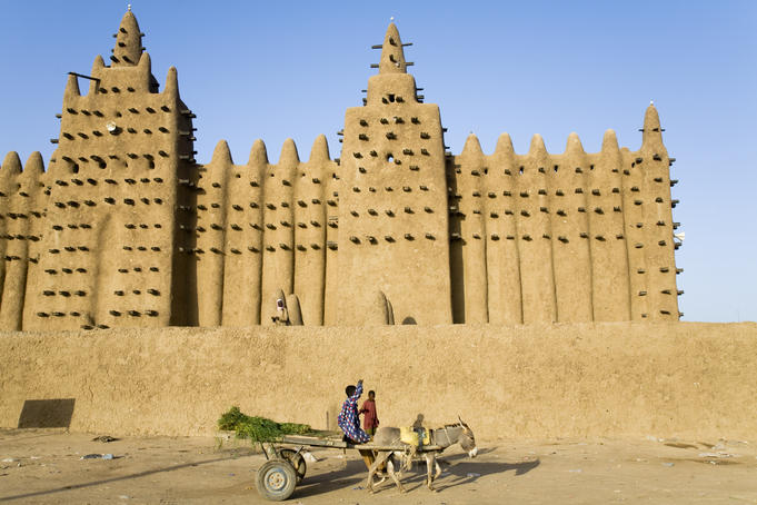 Young boy with donkey cart in front of the Grande Mosque du Djenne.