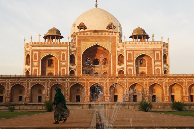 Woman wearing sari walking past Humayun's tomb in New Delhi.