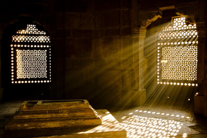 Shafts of early morning sunlight shining through lattice window into tomb of Isa Khan near Humayin's tomb in New Delhi.