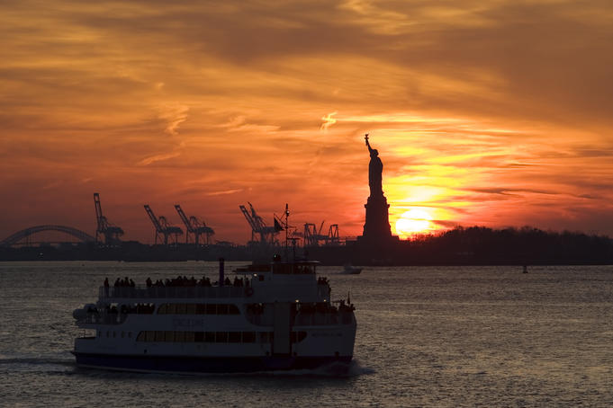 Statue of Liberty and Staten Island Ferry at sunset.