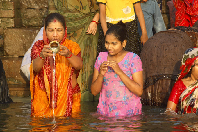 Pilgrims bathing and pouring holy water at ghat on river Ganges.