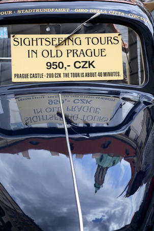 Sightseeing tour sign on windscreen of old car.