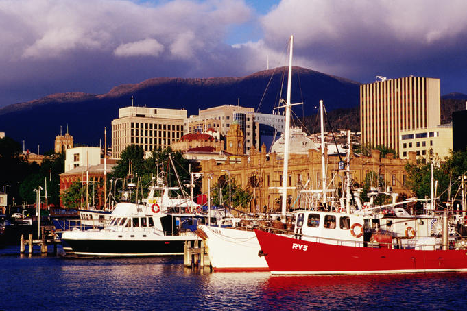 Boats at Victoria Dock with city buildings and Mount Wellington in background.