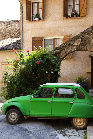 Old green Renault near house.