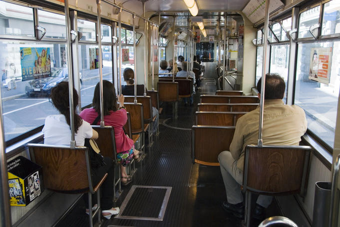 Passenger on wooden seats in an old Be 4/6 tram.