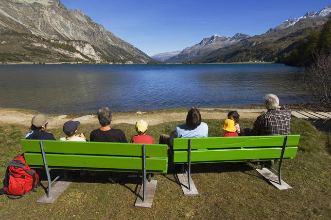 People sitting on green benches at alpine Silser See (lake).