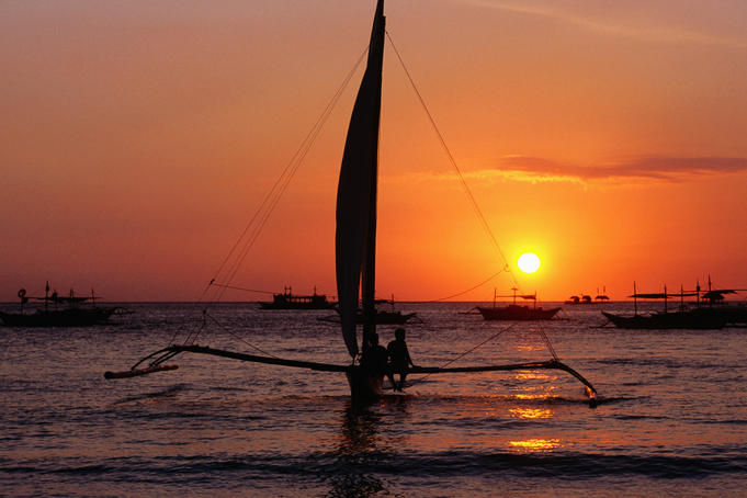Paraw (traditional outrigger sailboat) sailing at sunset.