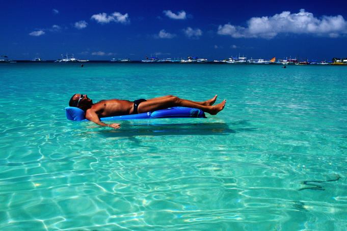 Tourist floating on airbed, White Beach.
