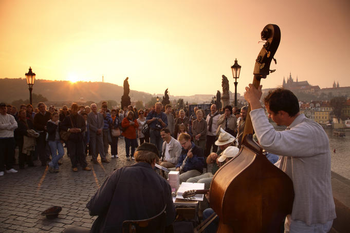 Tourists surround busker's near Charles bridge at sunset.