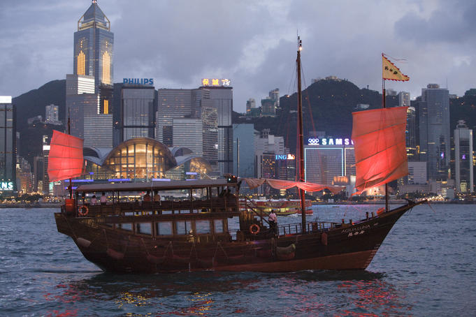 Traditional Chinese-style boat on Victoria Harbour with Hong Kong Convention and Exhibition Centre in background.