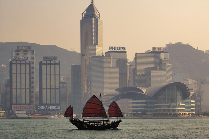 Sightseeing junk on Victoria Harbour with Hong Kong Convention and Exhibition Centre and Wan Chai skyline in background.