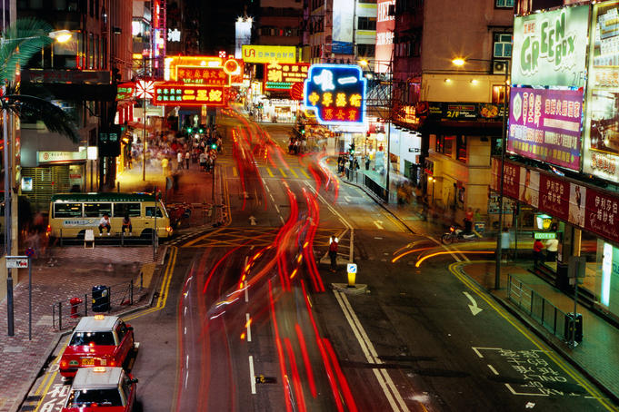 Traffic and neon signs in Causeway Bay at dusk.