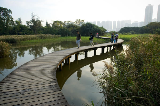 People on walking trail through the Hong Kong Wetland Park, Tin Shui Wai, New Territories.