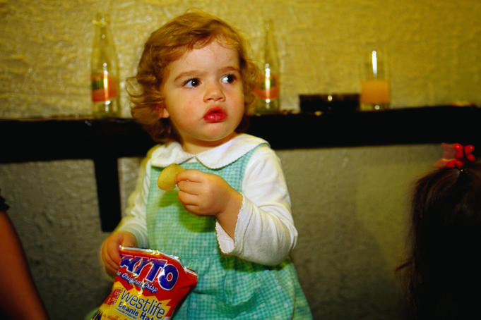 A young girl tucks into a packet of crisps - Dublin, County Dublin