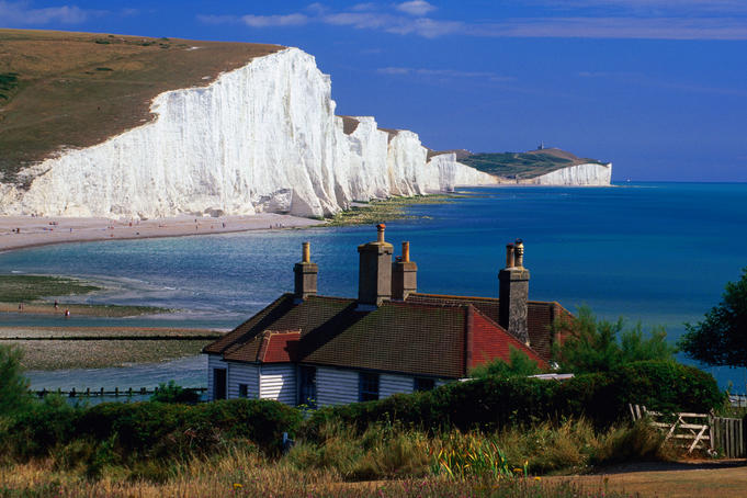Cottages with Seven Sisters cliffs in background, South Downs, East Sussex.